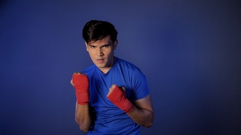 Time-lapse shot of an Indian fighter in blue clothes and bandages on the wrist punching