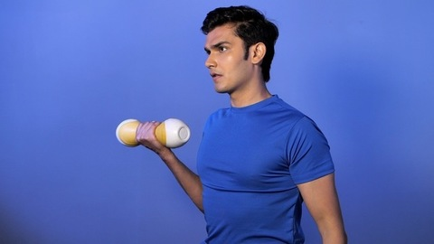 Fit Indian bodybuilder lifting weight dumbbells for biceps training - sports activity