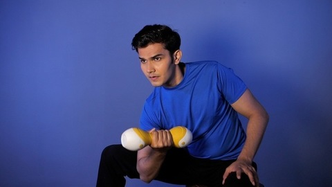 Sportsman exercising for arm muscles using dumbbell - fitness and health