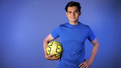 Portrait of a smiling sports person standing with a soccer ball - active lifestyle