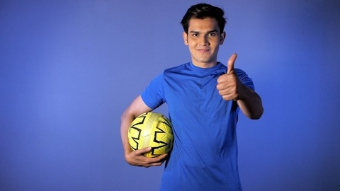Indian male showing thumbs-up sign while holding a football - active lifestyle