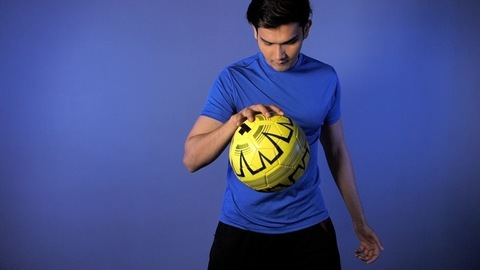 Indian muscular male in blue sportswear bouncing a soccer ball with hand indoors