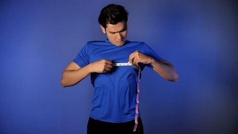 Portrait of a healthy youth measuring his chest size with a tape - weight loss