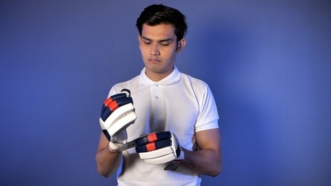 Portrait of young Indian cricket player wearing hand gloves and getting ready for game