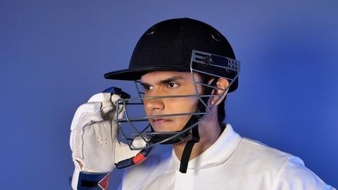 Portrait of an Indian male cricket batsman adjusting his helmet - sports concept