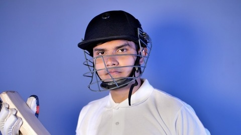 Portrait of a professional batsman looking at a cricket bat in his gloved hands