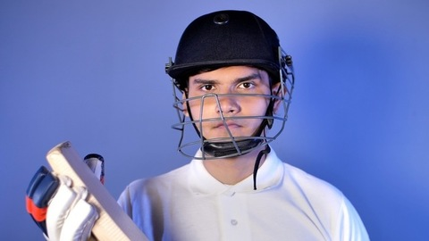 Portrait of a confident Indian cricketer wearing a helmet and holding a cricket bat