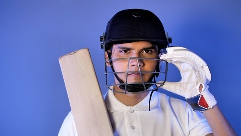 Indian cricket batsman with helmet, bat, and gloves in hands, looking at the camera - Sports
