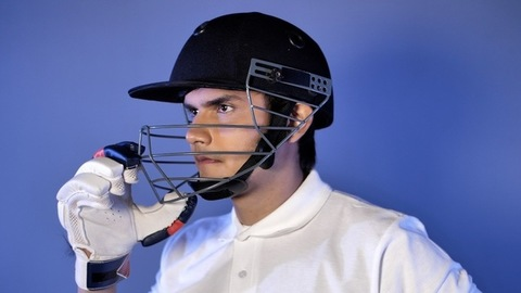 Young Indian cricketer adjusting his helmet in the dressing room - getting ready for the game
