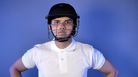 Indian batsman in full cricket uniform with helmet - fixing hand gloves before the game