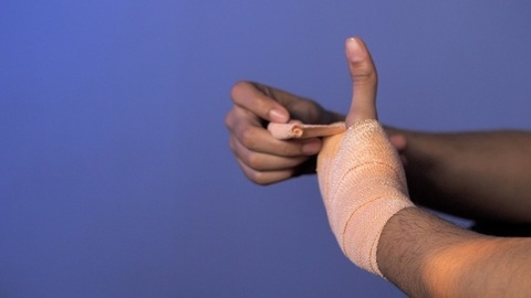 Wrist sprain - Young man wrapping crepe bandage on his painful wrist