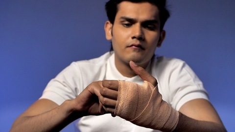 Indian male applying an elastic bandage for sprain - Indian boxer