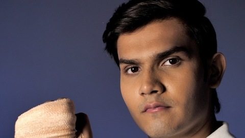 A clean-shaven confident youth with a medical supportive bandage on his hand