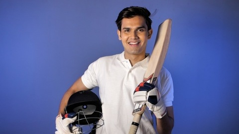 Indian cricketer in a white uniform with all cricket gears posing for the camera - sports activity