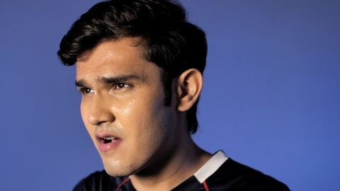 Sideview of a tired Indian athlete breathing heavily with sweat drops on his face