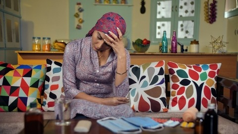 Sick Indian woman with her head covered with a scarf not feeling well at her home