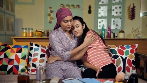 A cancer patient with covered head consoling her daughter at home