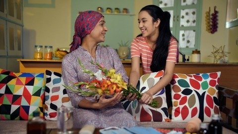 A young Indian girl gifts beautiful flowers to her mother suffering from cancer