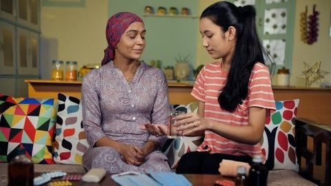 Indian teenager giving medicines to her mother suffering from cancer