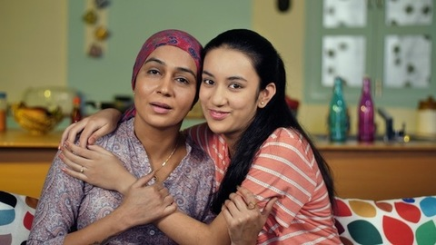 Young female cancer patient with her teen daughter at home making a video call