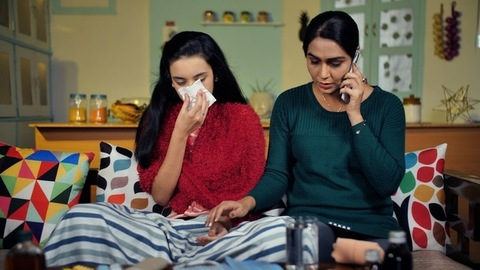 Mother taking doctors advice on mobile while caring for her sick daughter