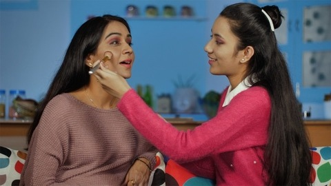 Teen daughter learning to apply makeup on her mother's face - Mother-daughter bonding