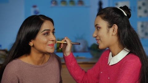 Indian girl using a makeup brush on the cheekbones of her mother - Mother Daughter Bonding