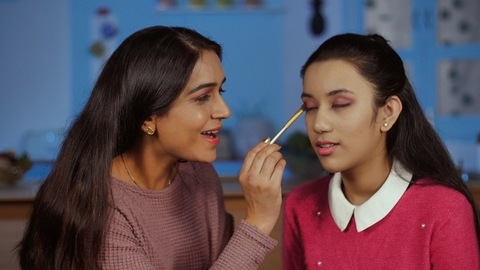 Indian mom doing her teen daughter's makeup - cosmetics and beauty