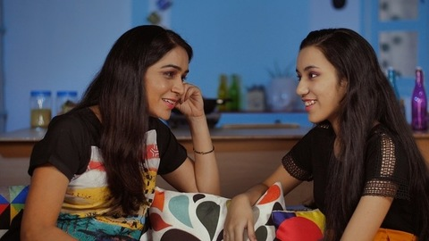 Two happy Indian females chatting while sitting on the sofa at home - family time