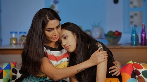 Worried Indian mother consoling her depressed teenage daughter at home