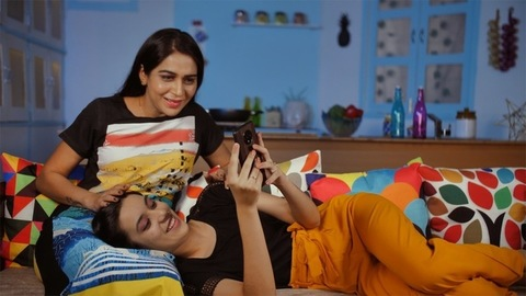 Indian teenage girl teaching her mother to use a mobile application at home