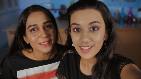 Attractive mother-daughter duo making a video call using a smartphone from home
