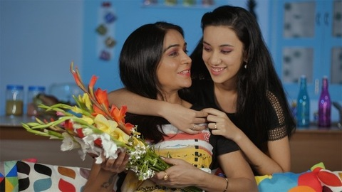 Teen daughter giving a beautiful bouquet to her mother - happy family moment