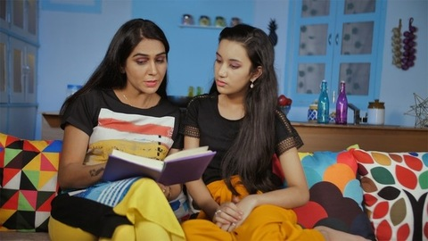 Mother teaching her teenage girl child at home - helping with studies concept
