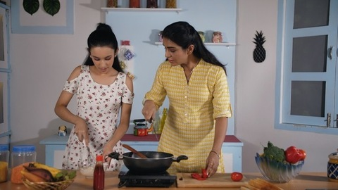 Caring mother teaching her teenage daughter interesting recipe at home kitchen