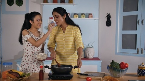 Two Indian females enjoying eating wafers while working in the home kitchen