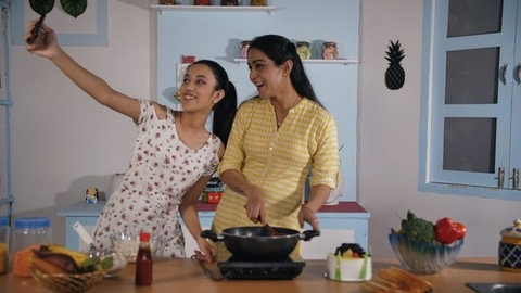 Mother-daughter taking selfies while making food in the kitchen - food concept