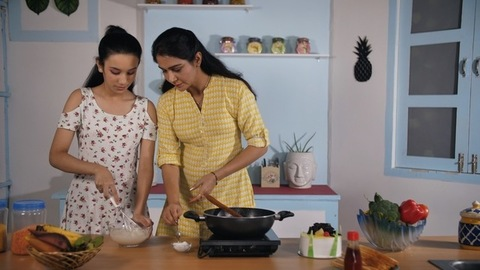 Indian mother teaching cooking to her teenage daughter - Family responsibility