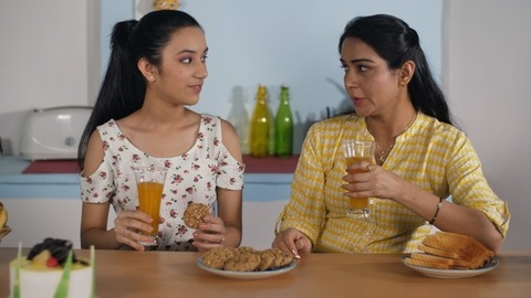 Indian mother and teenager daughter partying at home with healthy juice and cookies
