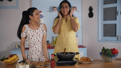 Lovely females enjoying music on a blue headphone while cooking in the kitchen