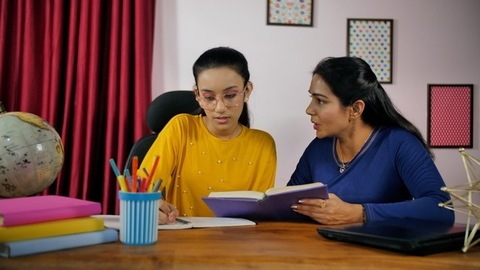 Smart mother helping her teenage child in studies while sitting in the study room