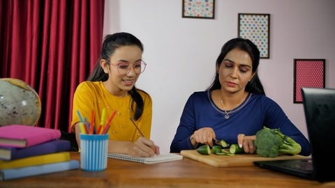 Indian mother talking to her teenage daughter while chopping green vegetables