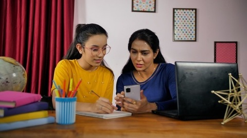 Mom teaching teenage daughter from mobile - Online learning. Edtech