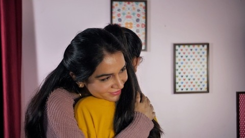 Young woman with long hair lovingly hugging a teenage girl - emotional moment