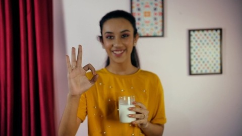 Healthy drink - Happy adolescent girl having fresh white milk at home
