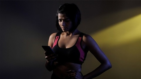 Woman using a mobile while resting during fitness training - a healthy lifestyle