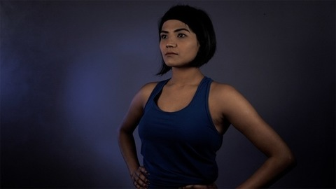 Portrait of a gymnast in blue clothes staring away from the camera - Indian athlete