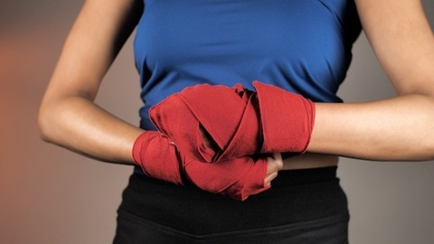 Indian female fighter wrapping boxing bandages - kickboxing training