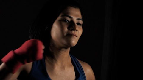 Female boxer hitting a punching bag while preparing for kickboxing training