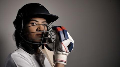 Confident Indian woman cricketer wearing batting gloves adjusting her safety helmet